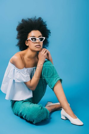 beautiful young woman in stylish off-the-shoulder top and sunglasses sitting on floor on blue