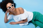 beautiful young woman in stylish clothes and sunglasses lying on floor on blue