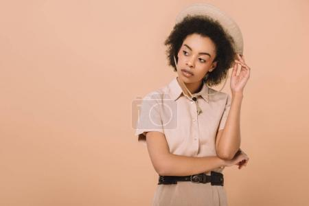 stylish african american woman in shirt and safari hat isolated on beige