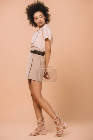 attractive african american woman in stylish clothes on beige