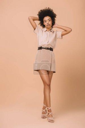 Photo pour Jeune femme afro-américaine dans des vêtements élégants sur beige - image libre de droit