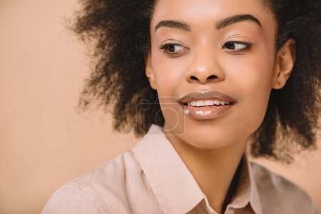 close-up portrait of happy young woman in stylish shirt isolated on beige