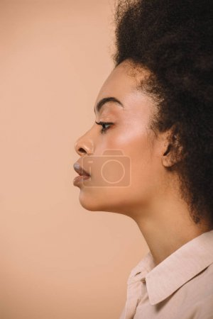 side view of attractive african american woman isolated on beige