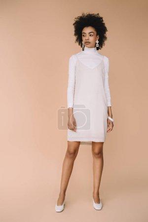 schöne junge Frau in stilvollem weißen Kleid auf beige