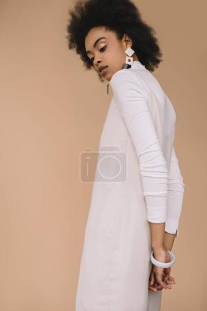 attractive young woman in white dress with earrings isolated on beige