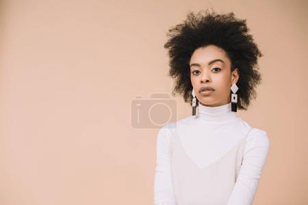 Photo pour Belle jeune femme à col roulé blanc, regardant la caméra isolée sur beige - image libre de droit