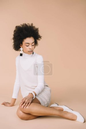 attractive young woman in stylish white dress and shoes sitting on floor on beige