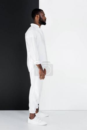 side view of stylish african american man standing in white clothes near black and white wall