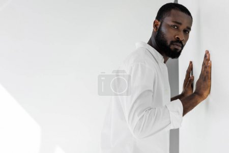 handsome stylish african american man in white clothes touching wall