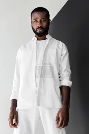 low angle view of handsome stylish african american man looking at camera in white clothes
