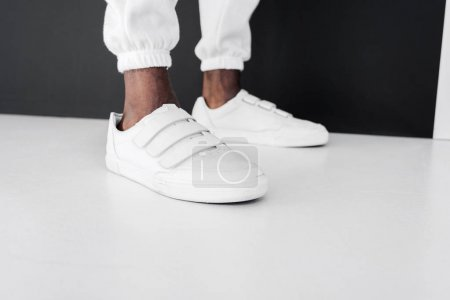 cropped image of stylish african american man standing in white gumshoes