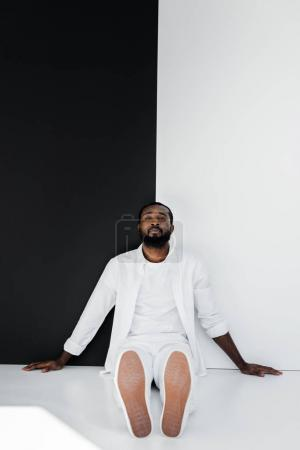 handsome stylish african american man sitting on floor near black and white wall and looking at camera