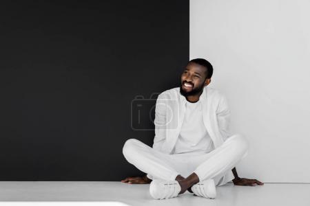 Photo pour Souriant homme afro-américain élégant assis sur le sol près du mur noir et blanc - image libre de droit