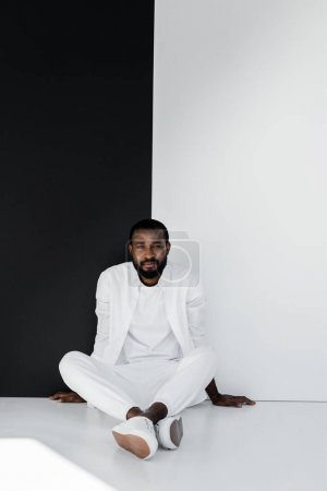 handsome stylish african american man sitting on floor near black and white wall
