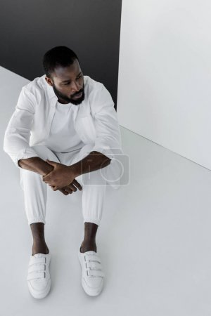 high angle view of handsome stylish african american man sitting in white clothes on floor