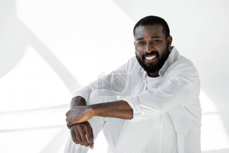 smiling handsome african american man in white clothes sitting and looking at camera on white