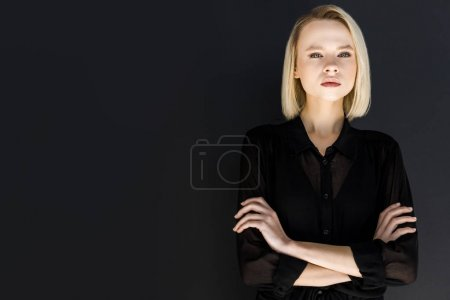 attractive stylish blonde woman in black clothes standing with crossed arms isolated on black