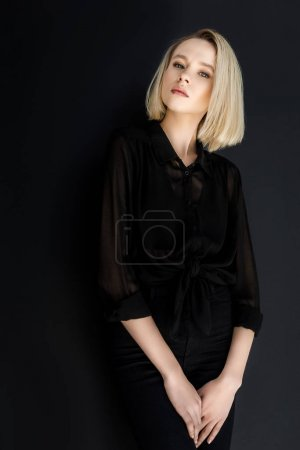 attractive stylish blonde woman in black clothes looking at camera isolated on black