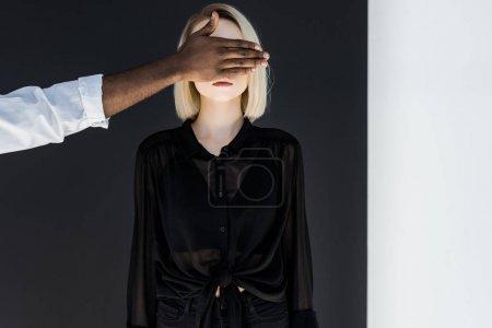 cropped image of african american boyfriend closing blonde girlfriend eyes, yin yang concept