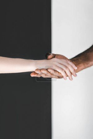 cropped image of multicultural couple holding hands near black and white wall