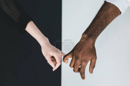 Photo for Cropped image of african american boyfriend and girlfriend holding fingers near black and white wall - Royalty Free Image