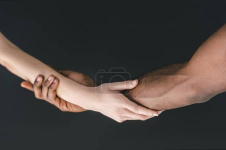 cropped image of multicultural couple holding hands isolated on black
