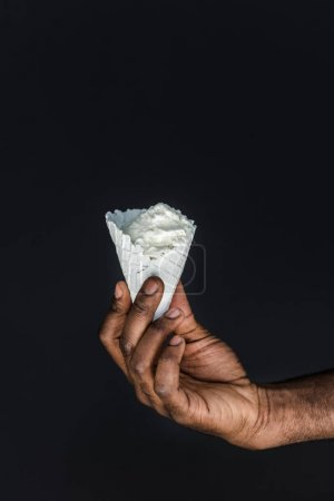 cropped image of african american man holding white ice cream cone isolated on black