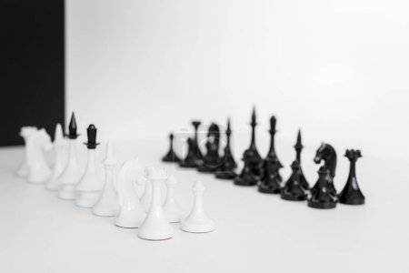 chess figures on white tabletop near black and white wall