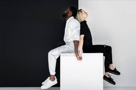Photo for Multicultural couple holding hands on white cube, yin yang concept - Royalty Free Image