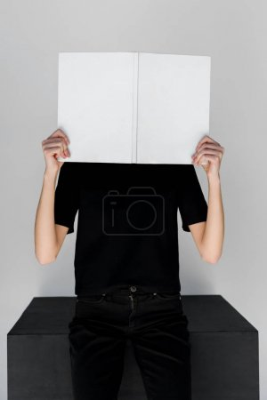 Photo for Stylish woman in black clothes covering face with white book isolated on grey - Royalty Free Image