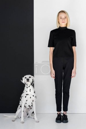attractive stylish blonde woman in black clothes standing near black and white wall with dalmatian dog