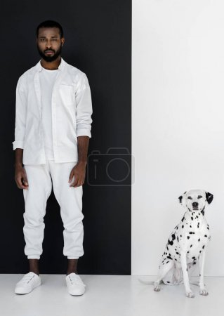 handsome stylish african american man in white clothes with dalmatian dog near black and white wall