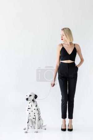 Photo pour Jolie femme blonde élégante en vêtements noirs tenant laisse dalmate chien sur blanc - image libre de droit