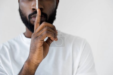 cropped image of african american man with white stripe on face showing silence sign isolated on white