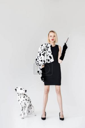 attractive stylish blonde woman in black dress holding cigarette, dalmatian dog on floor