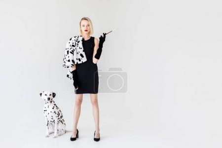 attractive stylish blonde woman in black dress with dalmatian dog on white