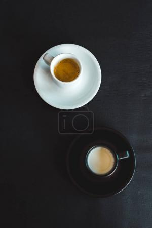 high angle view of black and white cups of milk and coffee on black surface