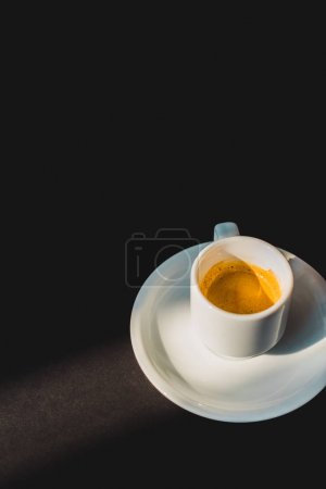 cup of tasty coffee in white cup on black surface
