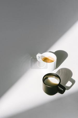 high angle view of black and white cups of milk and coffee on white surface
