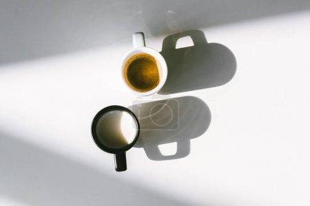 Photo pour Vue de dessus des tasses noires et blanches de lait et de café sur la table blanche - image libre de droit