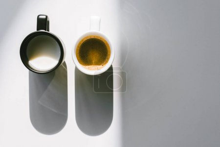 top view of black and white cups of milk and coffee on white tabletop