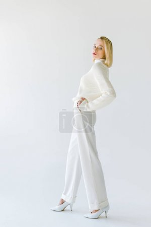 side view of beautiful stylish blonde woman in white clothes posing on white