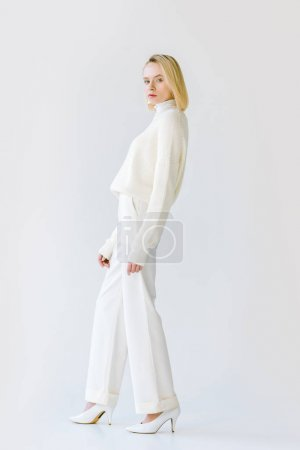 Photo for Side view of beautiful stylish blonde woman in white clothes looking at camera on white - Royalty Free Image
