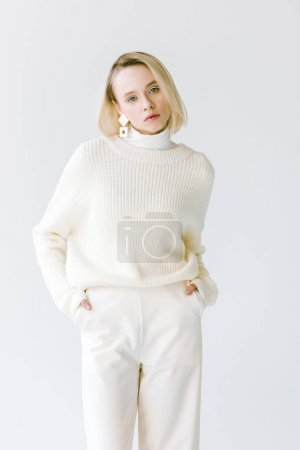 Photo pour Belle femme blonde élégante en vêtements blancs avec les mains dans les poches isolés sur blanc - image libre de droit