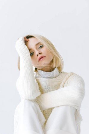 portrait of attractive fashionable blonde woman in white clothes looking at camera isolated on white