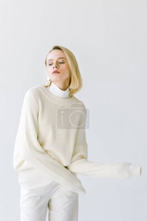 beautiful stylish blonde woman in white clothes looking down isolated on white