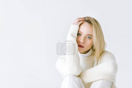 portrait of beautiful stylish blonde woman in white clothes looking at camera isolated on white