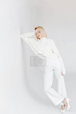 Photo for Beautiful stylish blonde girl in white clothes leaning on white wall - Royalty Free Image