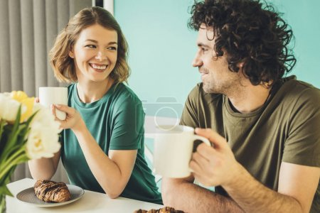 Foto de Feliz pareja sostener tazas y sonriendo unos a otros mientras desayunando juntos - Imagen libre de derechos