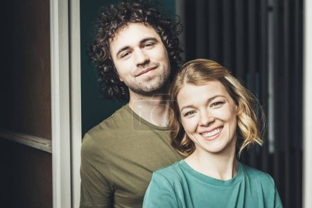 portrait of happy young couple smiling at camera together at home